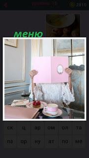 за столом девушка рассматривает розовое меню в кафе
