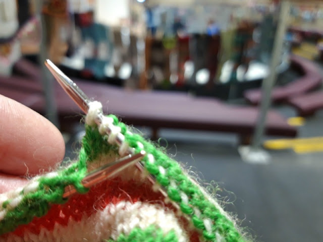A photo showing a sock being knitted in red, white and green striped yarn (West Yorkshire Spinners Candy Cane) with a view of the Yarndale Sock Line socks pegged to the washing line in the background.  The background socks are blurred as the picture focuses on the knitting in my hands.