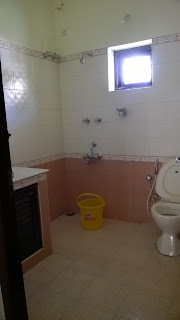 Another bathroom in a house in Kerala, India. No shower curtain or rod, equipped with a water sprayer.