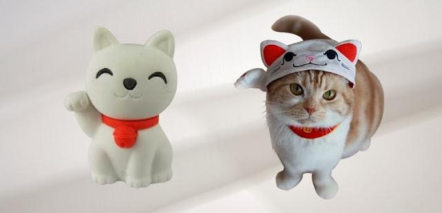 Escultura blanca de maneki neko, y gato disfrazado de maneki neko