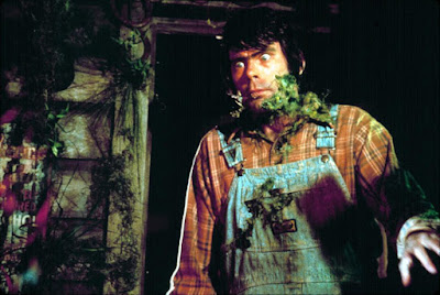 Jordy Verrill (Stephen King) is covered in grass and vines after touching a meteor in a movie still for the 1982 anthology film Creepshow