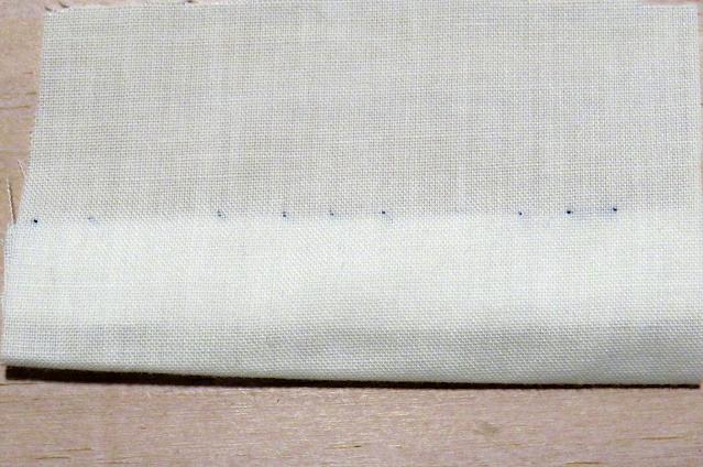 Puntada invisible con hilo azul sobre tela blanca por el derecho