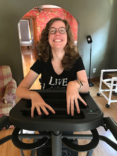 Image: Me smiling in my stander, fingers fanned on a tray