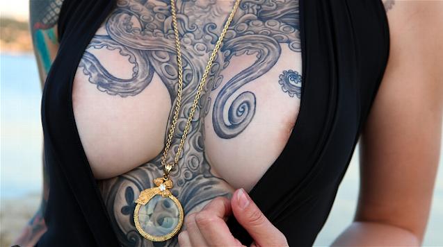 Mulher com uma tatuagem de polvo dominando seu colo e seios