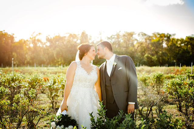 bride and groom on farm at sunset