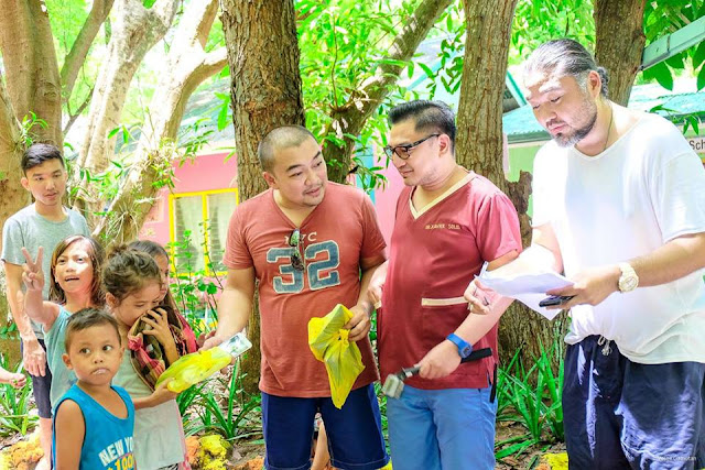 Doc. Xavier Solis (center) handing over some educational supplies