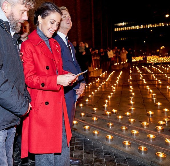 The Danish AIDS Foundation at Trinitatis Church in Copenhagen. candle lighting event, She wore a red wool coat by Maje