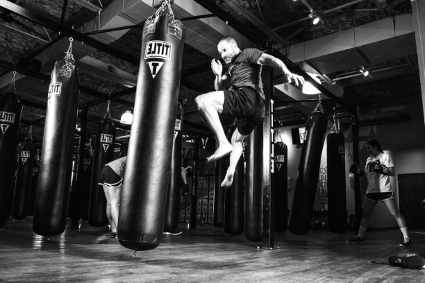 man kicking punching bags