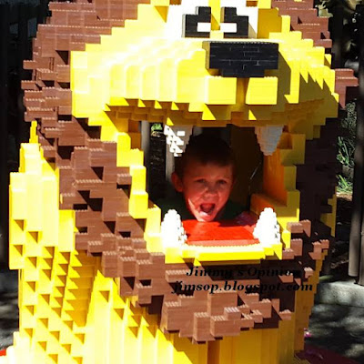A yellow lion made of lego bricks with our grandson Benjamin faking like he is screaming from inside it's mouth.
