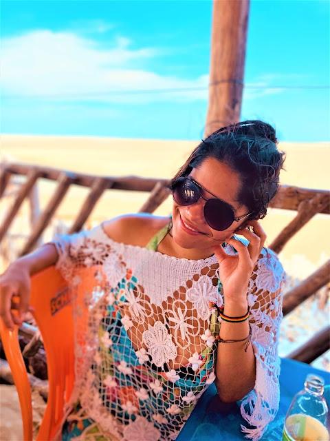 mulher sentada em uma cadeira de praia laranja, saida de banho de tricô branca, oculos escuros e cabelos pretos