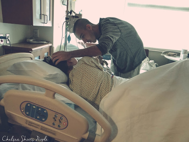 Husband checks on his wife lovingly in the hospital while waiting for the baby to arrive. photography