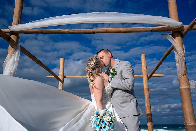 Bride and Groom kissing under beach arch way