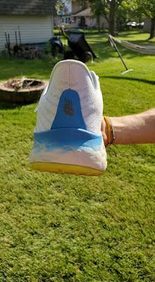 Direct heel view of the Vongo V5. A dense blue section digs into center of heel with NB vertically written.