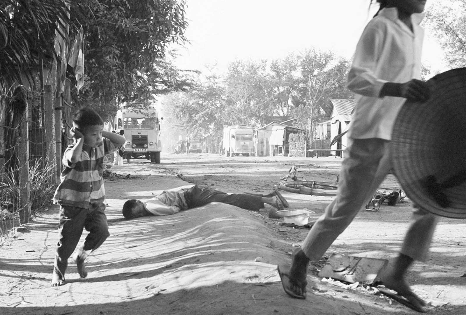 A dead civilian lies nearby as a young Vietnamese boy shields his ears from gunfire blasts and runs for cover on a Da Nang street on January 31, 1968.