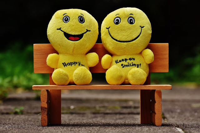 Two yellow smiley dolls on a park bench