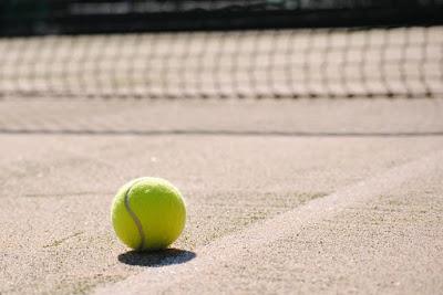 Grön tennisboll på grusbana med nät i suddig bakgrund.