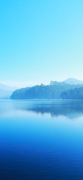 خلفية بحيرة المياه الزرقاء الهادئة في أحضان الطبيعة