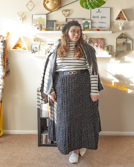 An outfit consisting of a black beret, a black faux leather moto jacket laid over the shoulders over a white with black horizontal striped turtleneck sweater tucked into a white on black micro polka dot pleated midi skirt and white mules.