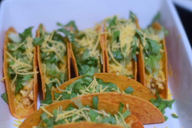 More shredded cheese being added to the tacos.