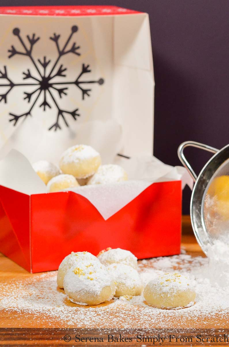 Lemon Snowball Cookies in a pile in front of a red box filled with powdered sugar coated Lemon Snow Ball Cookies