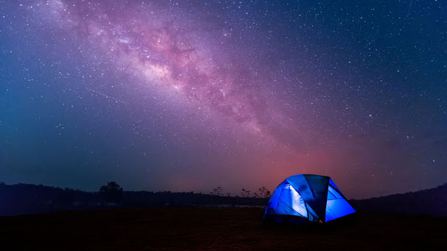 tent set up beneath night sky