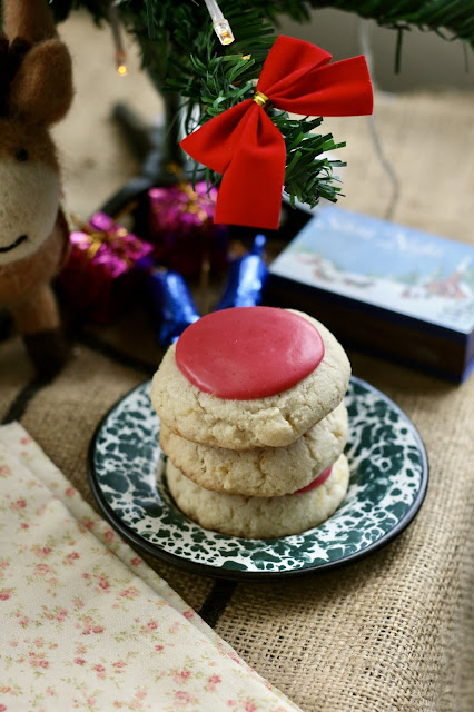 3 almond cookies stacked on top each other topped with a bright pink cranberry glaze