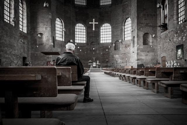 Man sitting in large grey church