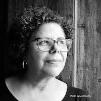 Mulher, usando óculos e com cabelos cacheados e foto preto e branco