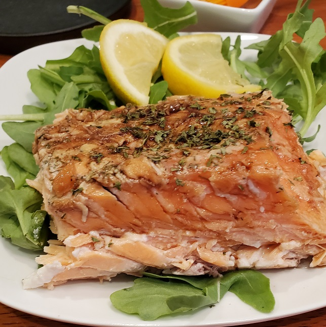 a large piece of grilled lemon butter salmon on a white plate with arugula underneath it