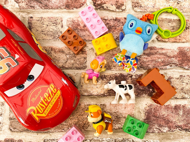 Selection of toys laid out including cars, Paw Patrol figures and duplo