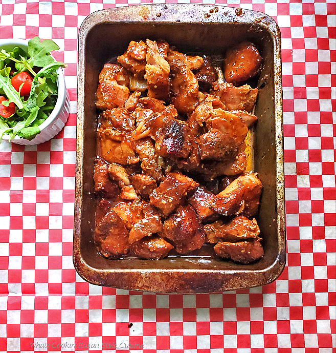 This is an old roasting pan that has pork cubed made into burnt ends. It is glazed with a sweet shiny apricot, barbecue hot sauce and has a arugula salad with tomato on the side. This pan sits on a checkerboard napkin style paper