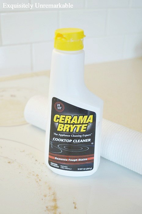 Cerama Bryte Cooktop Cleaner with a roll of paper towels on the dirty stove top