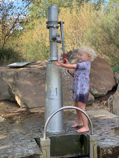 A 3 year old in a very wet dress pumping water at Tumbling Bay Playground