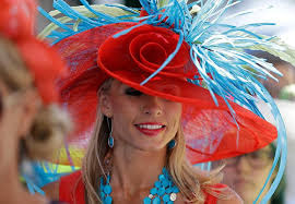 large derby hat with red rose in center and blue feathers on top worn by women with long blond hair and torqouis earrings and necklace