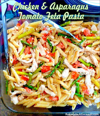Chicken and Asparagus Tomato Feta Pasta, a version of tomato feta pasta with all of the flavors of the original, and the addition of vegetables, protein, and a little kick. | Recipe developed by www.BakingInATornado.com | #recipe #dinner