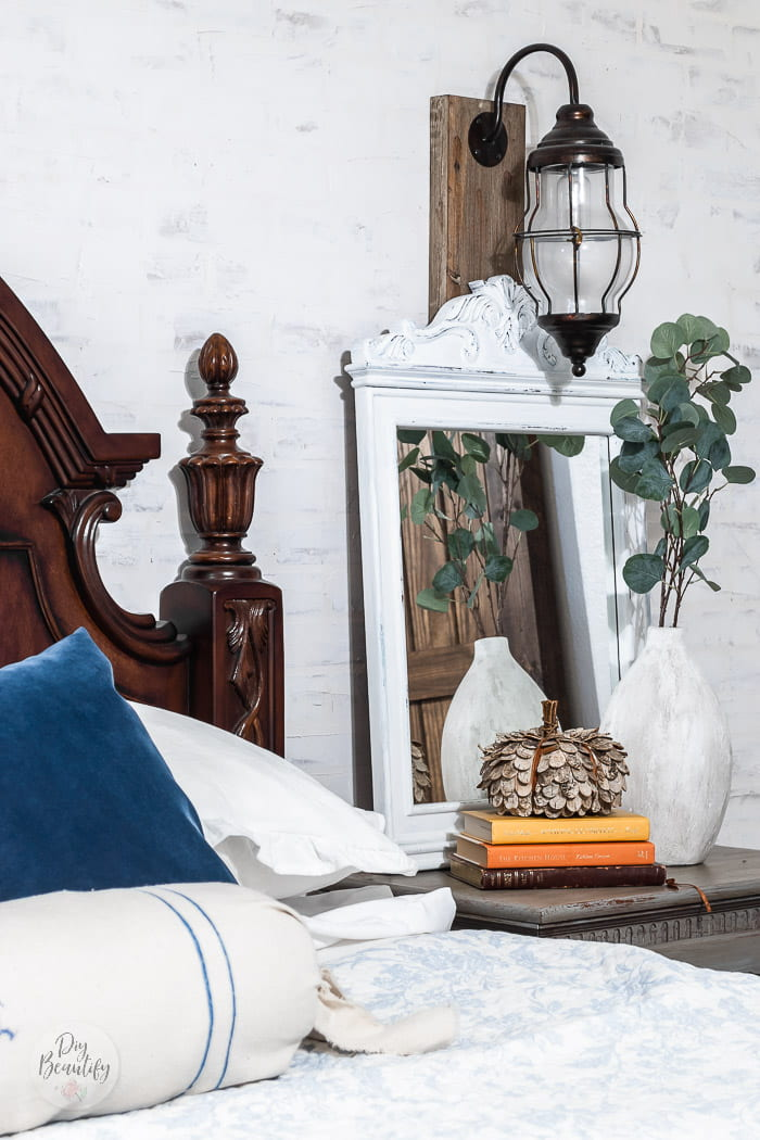 nightstand with mirror, white vase and greenery, rustic pumpkin and stack of books