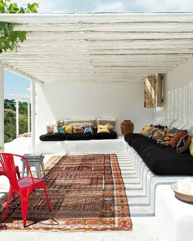 terraza con muebles de obra y alfombra oriental