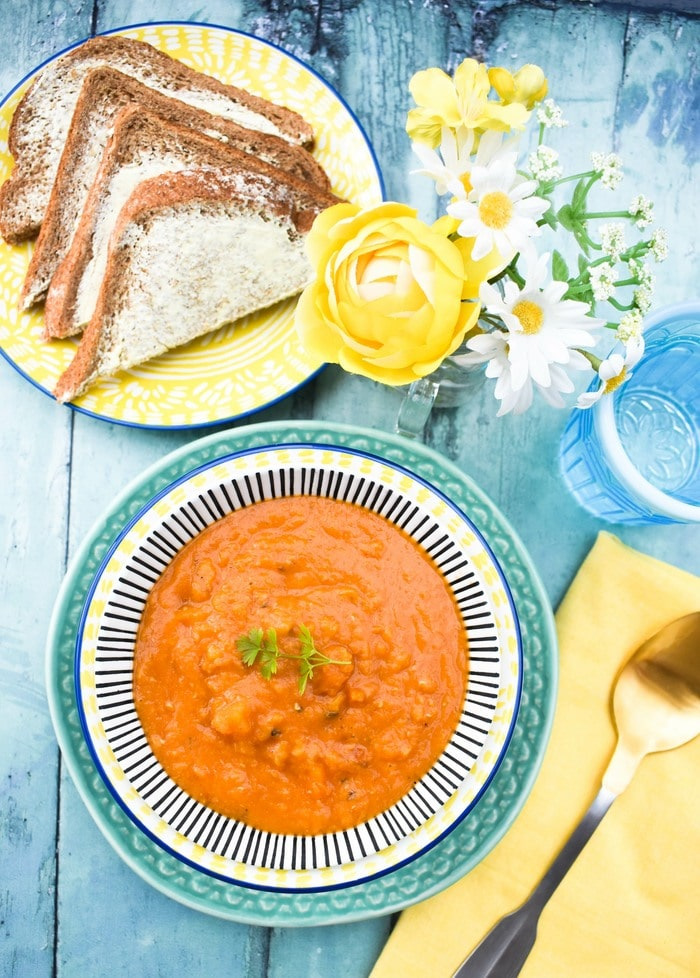 Overhead shot of lentil soup in a stripy bowl beside yellow flowers and a plate of buttered brown bread