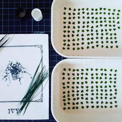 1/12 scale ivy plant kit instructions laid out on a cutting mat alongwith two small white trays holding q total of 245 teeny tiny ivy leaves, arranged neatly in rows.