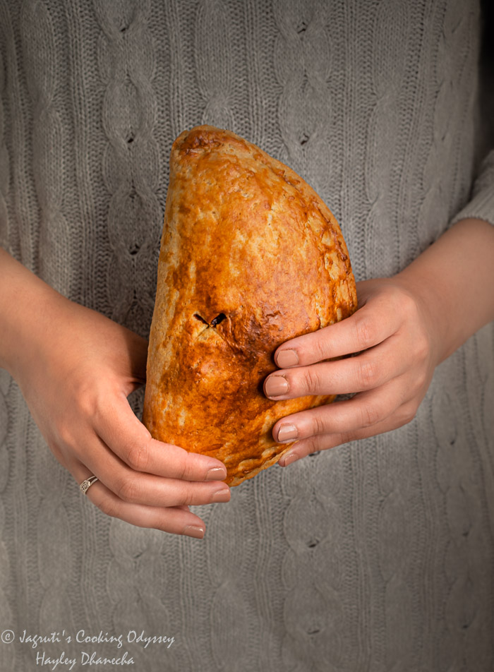 A girl is holding vegan flaky cornish pasty in her hands
