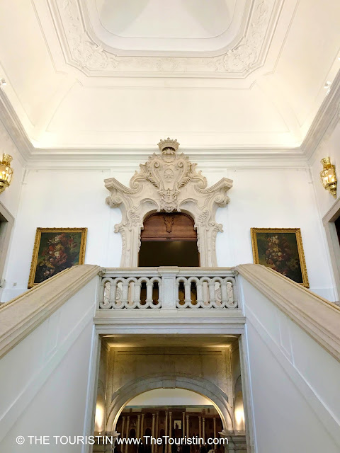 Grand staircase with ornamented door frames and golden decoration..