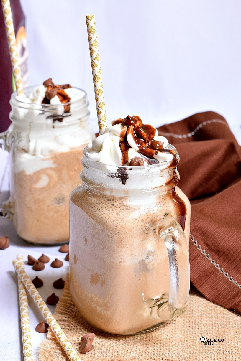 Close up of a mason jar having Banana Chocolate Frappe topped with whipped topping,chocolate sauce and chocolate chips