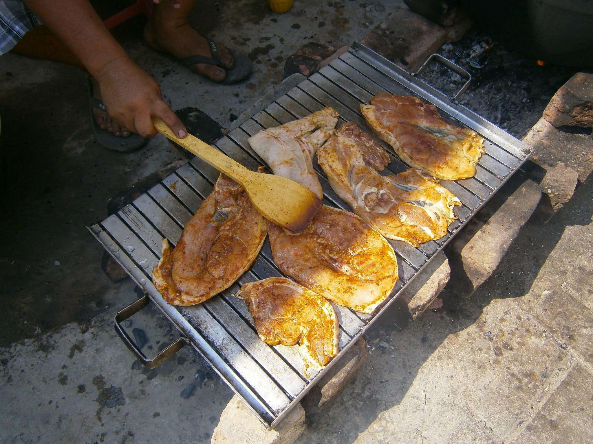 Parrilla de chancho hecha sobre una parrilla cocinado con carbón en Perú