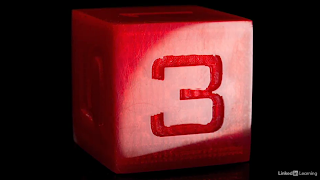 "A 3d printed 6-sided die shows the number ""3"". The die is shiny and red."