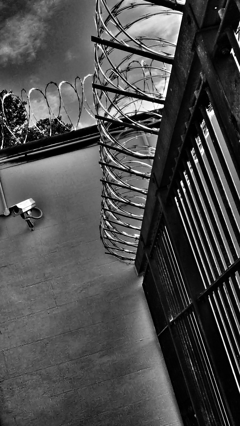 Tilted black and white photo of a prison wall