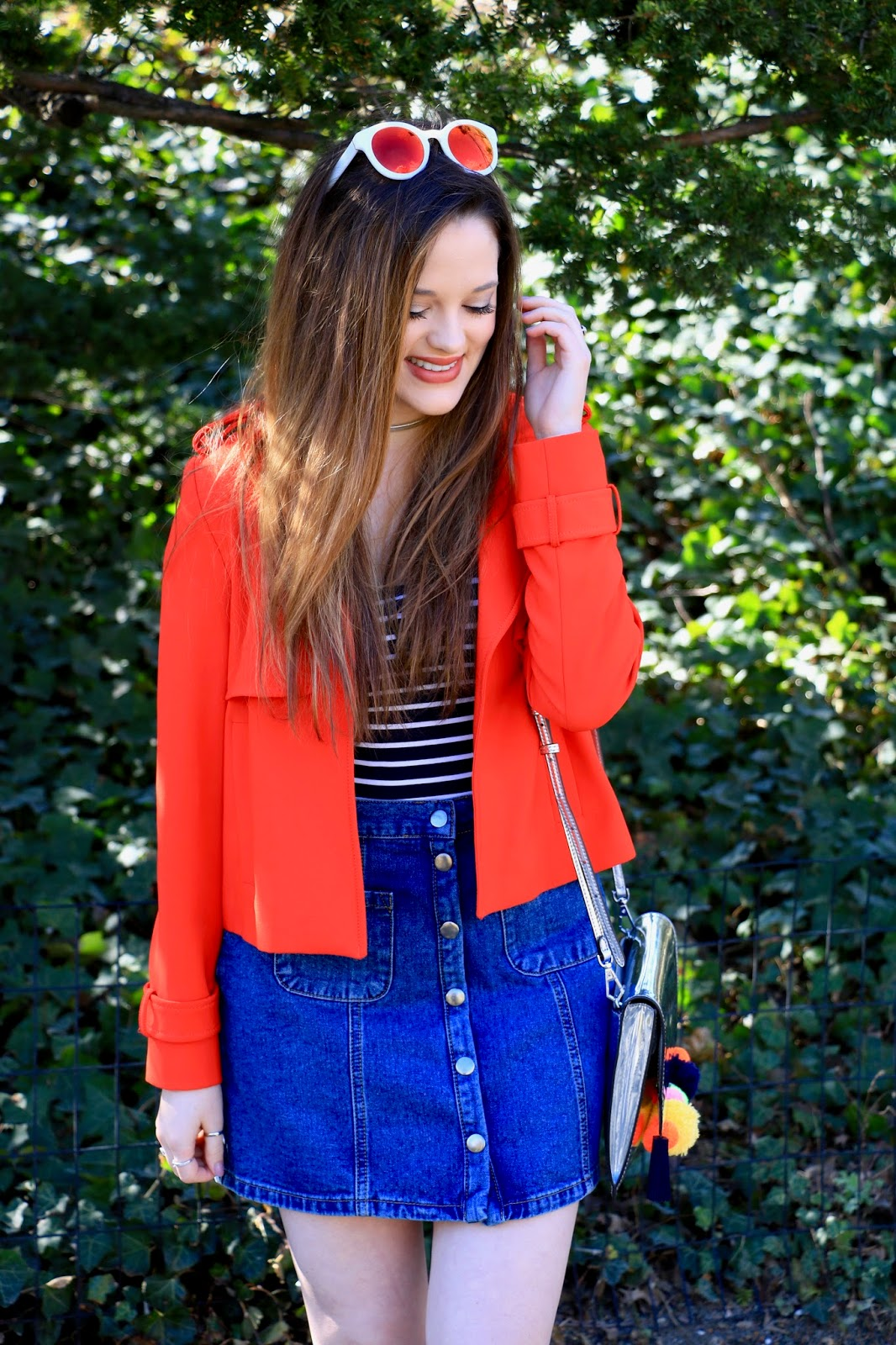 a fashion blogger wearing a denim skirt with a striped bodysuit and orange jacket