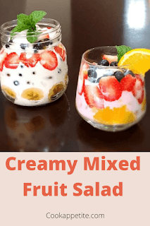 A simple fruit salad is the perfect side dish. It's great for serving for any time of the day. Glass Jars of blueberries,strawberries,grapes,bananas,orange,fruit loops,sour cream with mint on top. This simple mixed fruit salad is nutritious and easy to make.