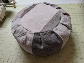 Slanted view of stuffed dark gray and off-white round meditation cushion