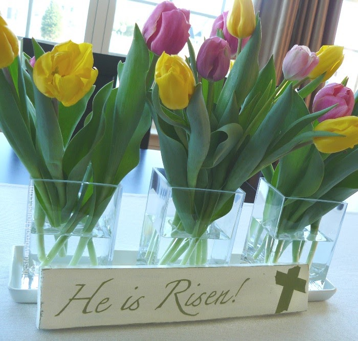 He Is Risen Sign in front of tulips