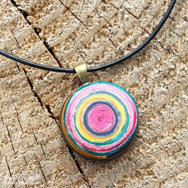 Rolled paper upcycled scrap papers pendant coated with glossy jewelry resin.